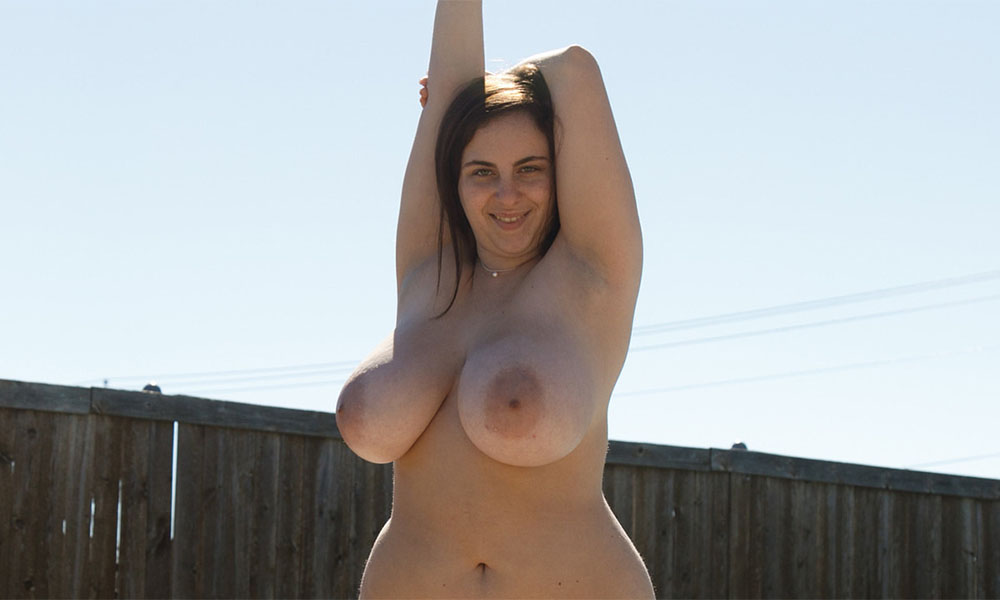 Curvy naked babe outdoors with big natural tits